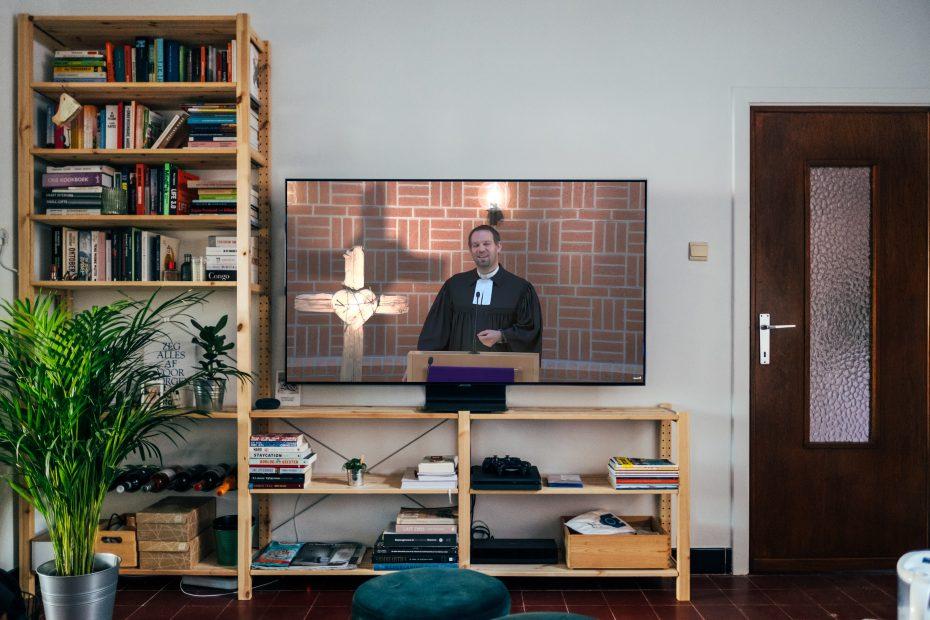 Auf einem Fernsehgerät läuft ein Gottesdienst-Livestream