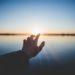 Eine Hand streckt sich dem Sonnenaufgang entgegen