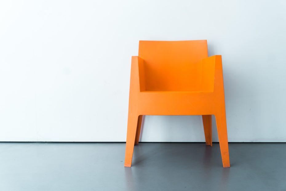 Ein oranger Stuhl vor einer weißen Wand