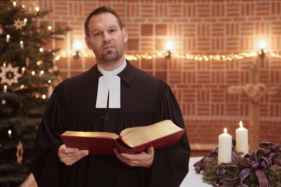 Pastor Marc Gommlich steht mit einer Bibel vor dem Weihnachtsbaum.